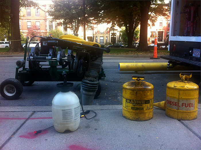 Chemicals litter the street as construction workers pave the street.